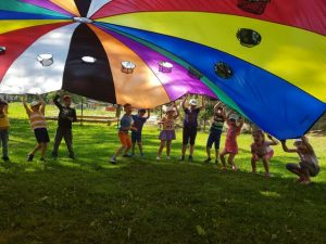vaikai žaidžia su parašiutu